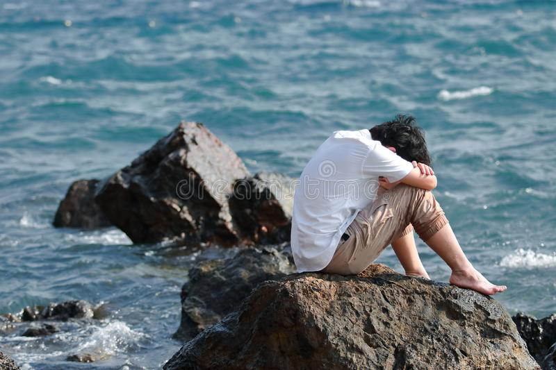 Depressed upset young Asian man covering face with hands sitting on the rock of sea shore stock images