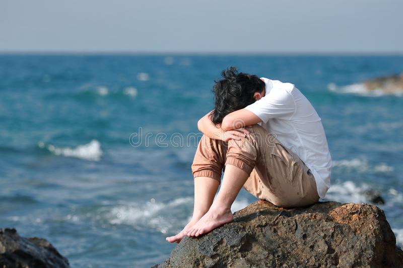 Depressed upset young Asian man covering face with hands sitting on the rock of sea shore.  stock photography