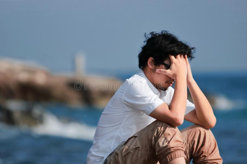Depressed upset young Asian man covering face with hands sitting on the rock of sea shore stock photo