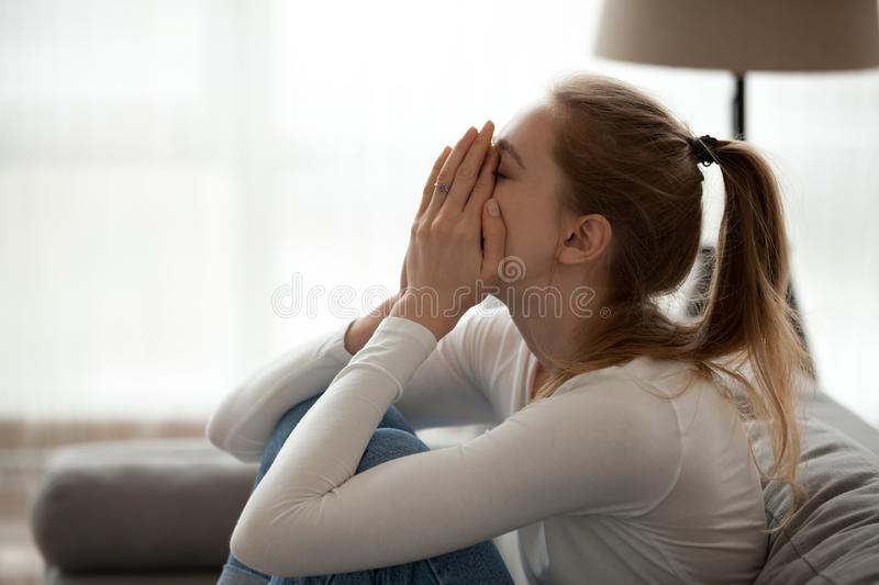 Depressed upset young woman crying alone at home stock photography