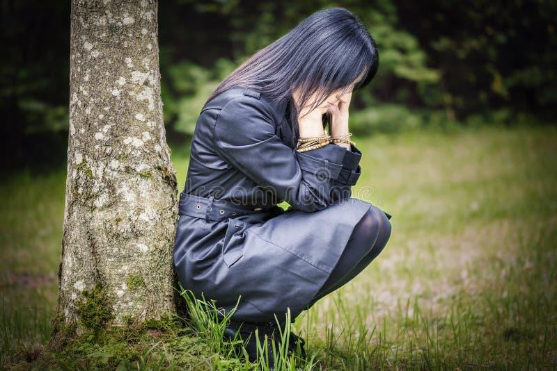 Depressed woman in focus near tree stock photos