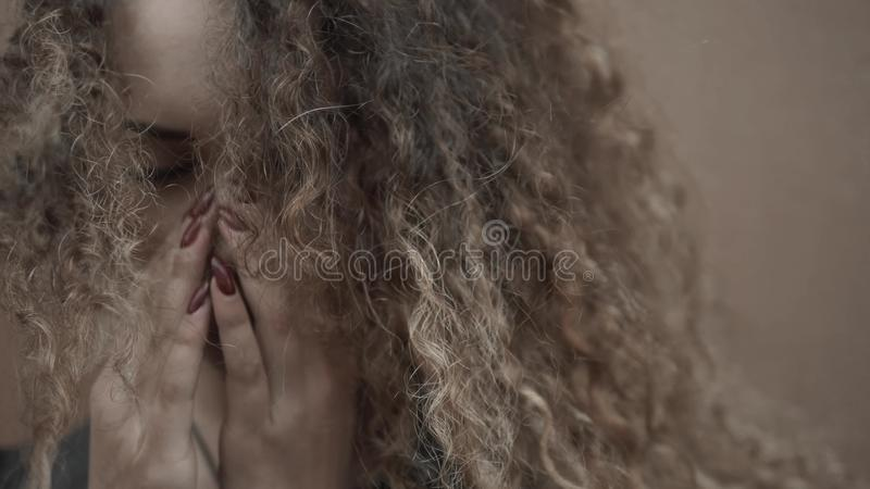 Depressed woman holding face in hands, young crying girl student close up, emotional portrait with tears. Depressed woman holding face in hands stock photography