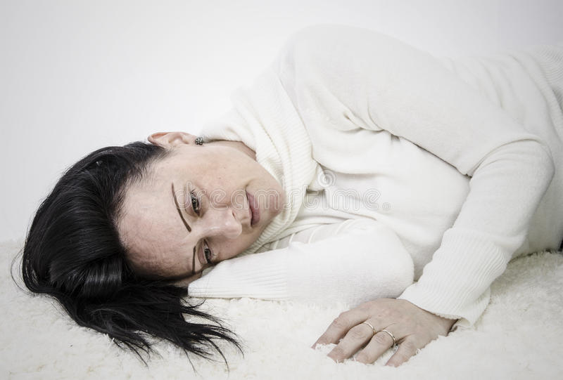 Depressed woman lying on floor stock photos
