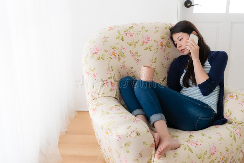 Depressed woman sitting in front of window sofa. Young depressed woman sitting in front of window sofa chair crying and using mobile smartphone calling for royalty free stock photo