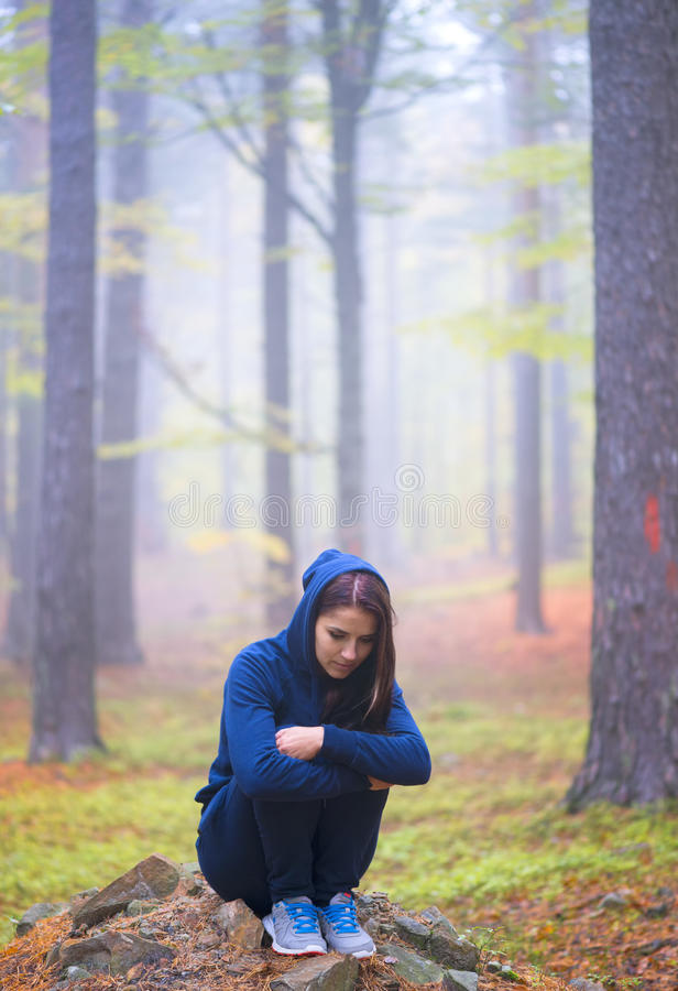 Depressed woman standing alone in forest in autumn stock photo