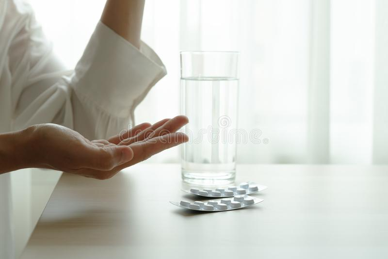Depressed women hand hold medicine with a glass of water, healthcare and medicine recovery concept royalty free stock photo
