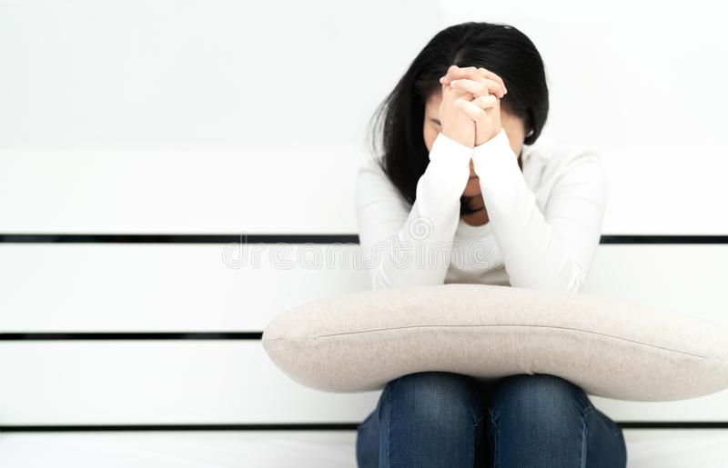 Depressed women sitting and pray in the room, alone, sadness, emotional concept stock image
