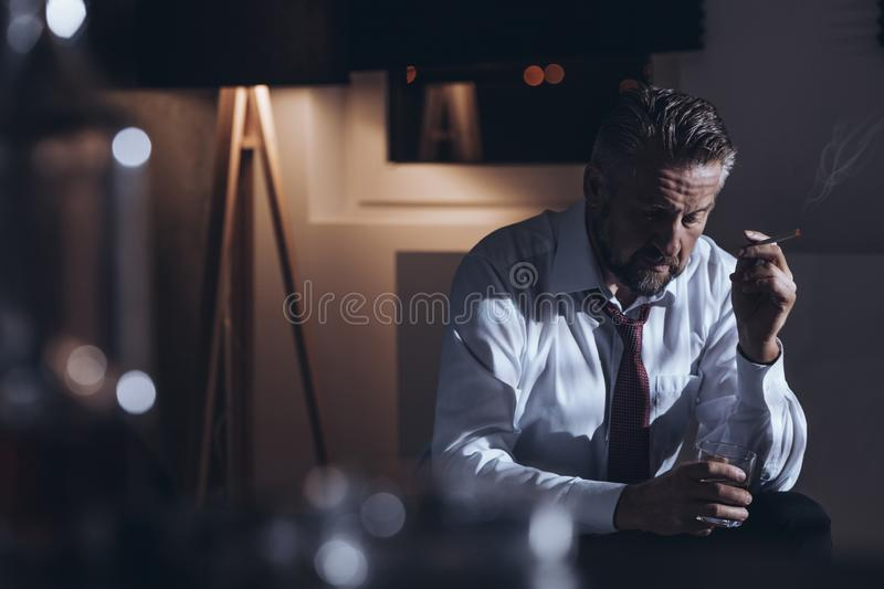 Depressed workaholic smoking cigarette. Depressed workaholic smoking a cigarette and drinking alcohol alone in a dark room royalty free stock photography