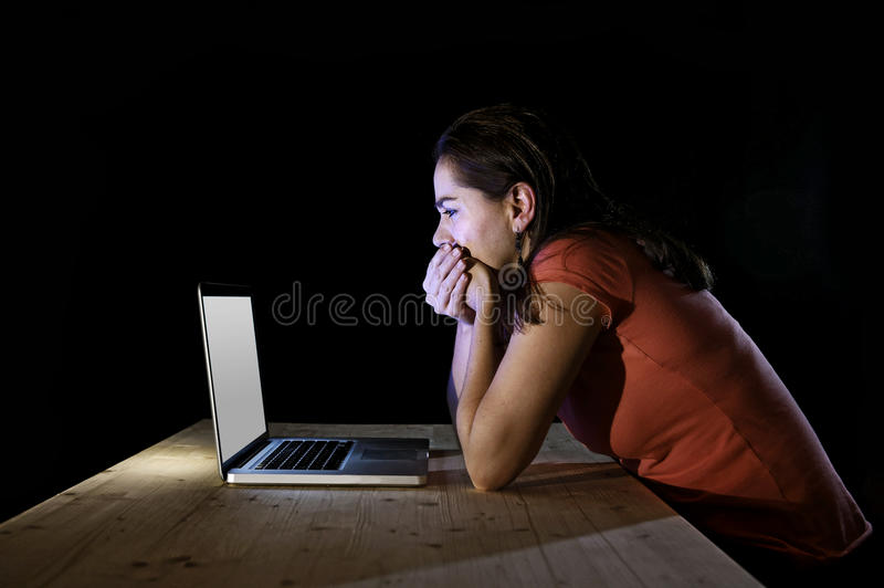 Depressed worker or student woman working with computer alone late night in stress. Young desperate and depressed freelance worker or student woman working with royalty free stock photo