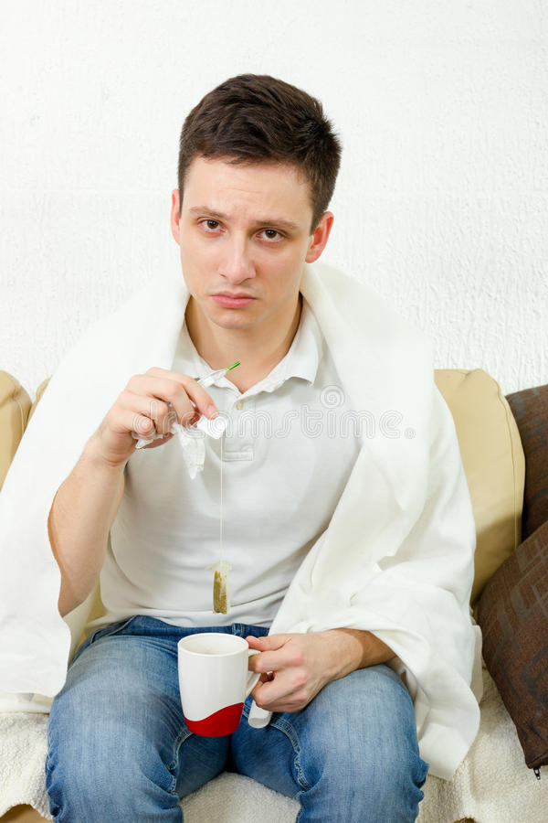 Depressed young adult man. Wathcing at camera while holding thermometer and tea bag. Sickness at home, recovery treatment. Male covered with blanket indoor stock image