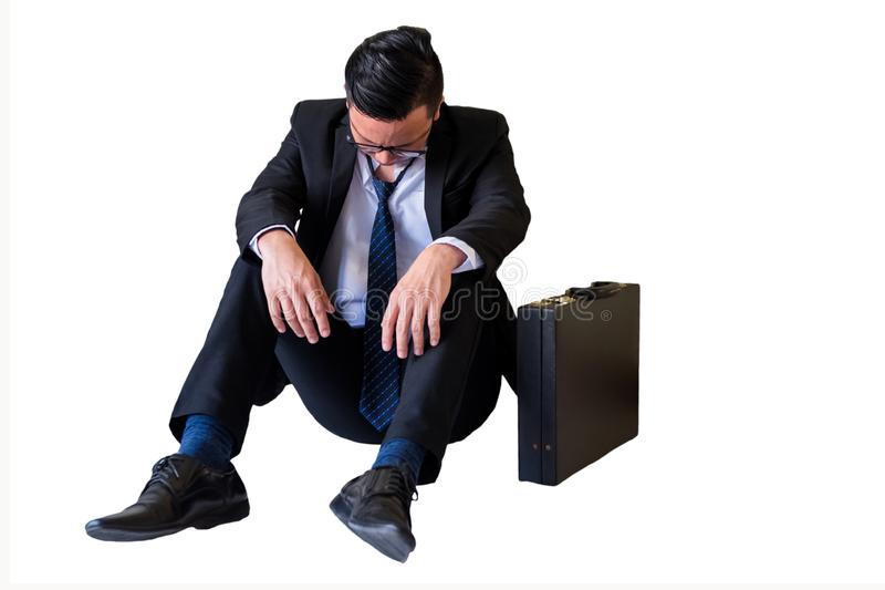 Depressed young Asian businessman isolated on white. Depressed young Asian businessman with glasses give up and sit on floor isolated on white background stock photography