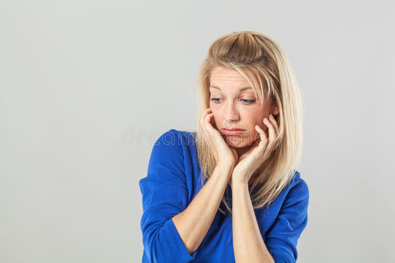 Depressed young blond woman looking down, expressing sadness and concern stock photography