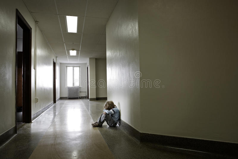 Depressed young boy sitting alone in a hallway royalty free stock image