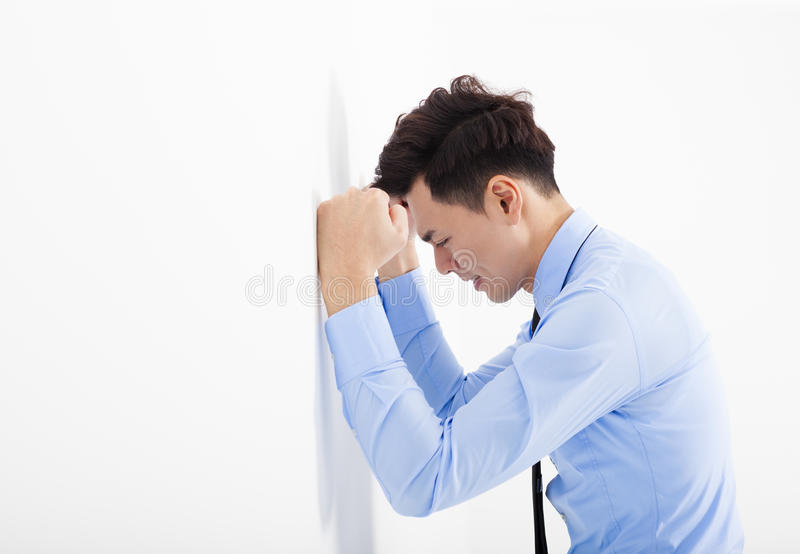 Depressed young business man leaning at the wall in office stock image