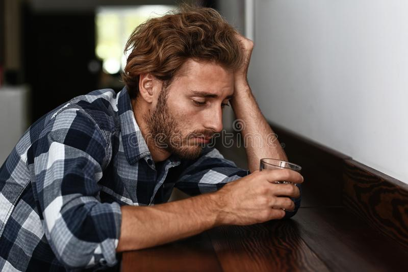 Depressed young man drinking alcohol in bar stock photos