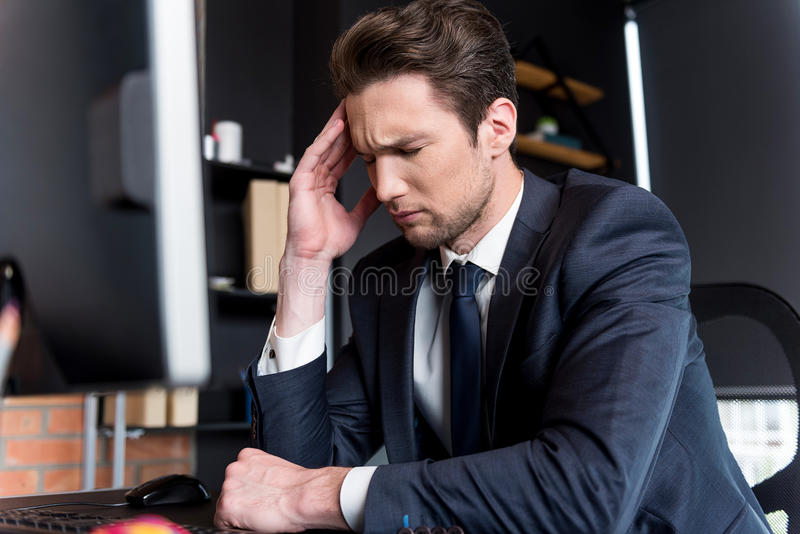 Depressed young man is having headache royalty free stock photography