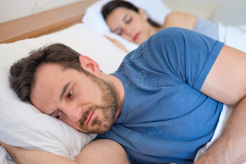Depressed young man lying in bed and having problems with his girlfriend stock photos