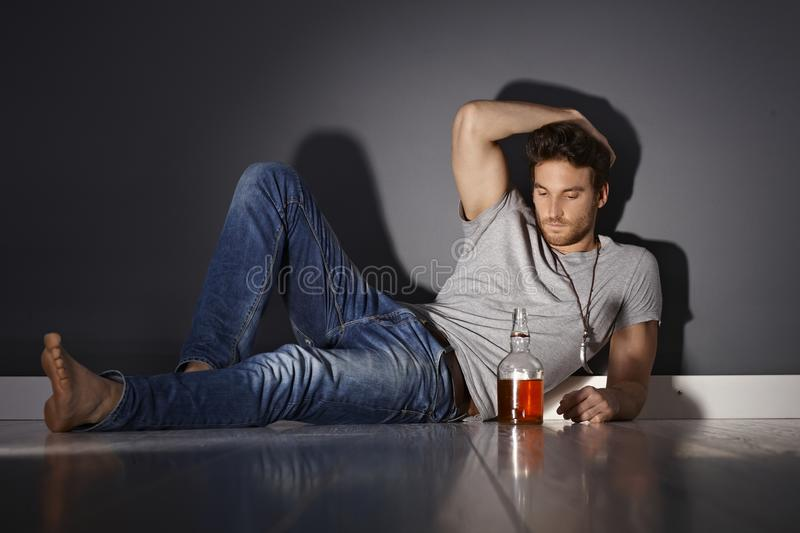 Depressed young man. Lying on floor, drinking alone stock image