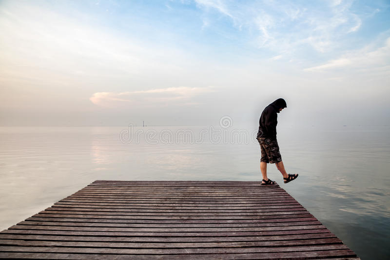 Depressed young man wearing a black hoodie standing on wooden bridge extended into the sea looking down and contemplating suicide stock photo
