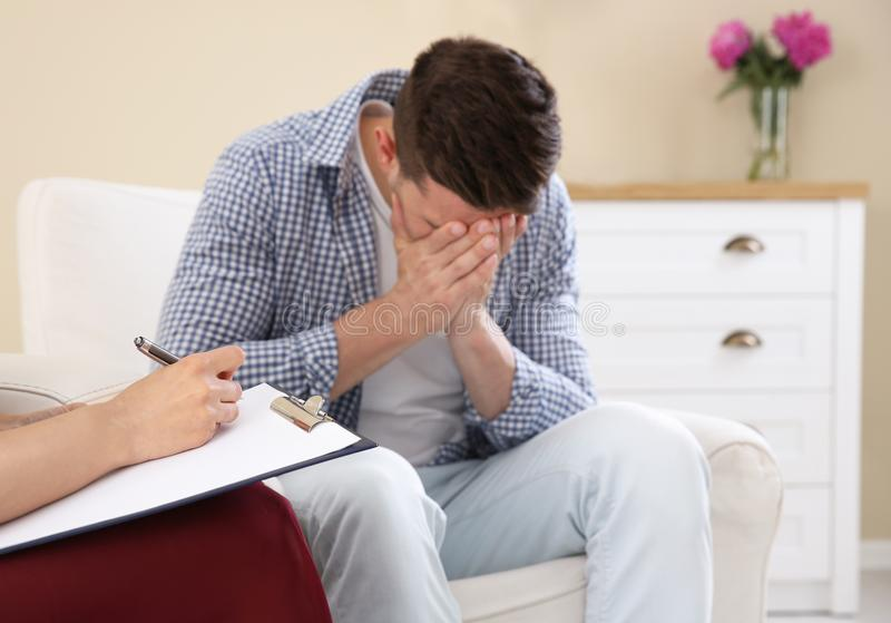 Young man having appointment with psychologist in office. Depressed young men having appointment with psychologist in office royalty free stock photography
