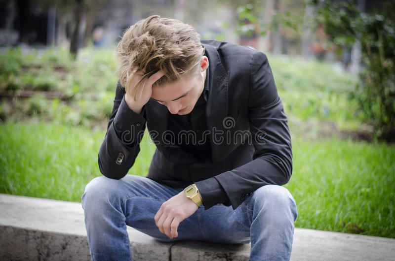 Depressed Young White Man Sitting at Street Side royalty free stock photography