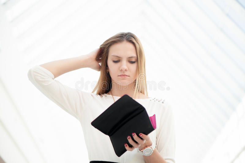 Depressed young woman looking into her purse in dismay stock photo