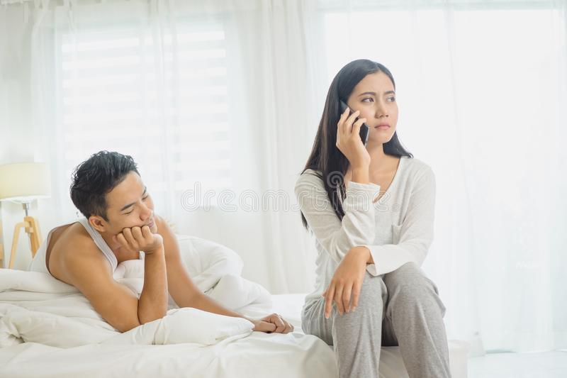 Depressed young woman sitting on bed calling on phone having problems with boyfriend stock image