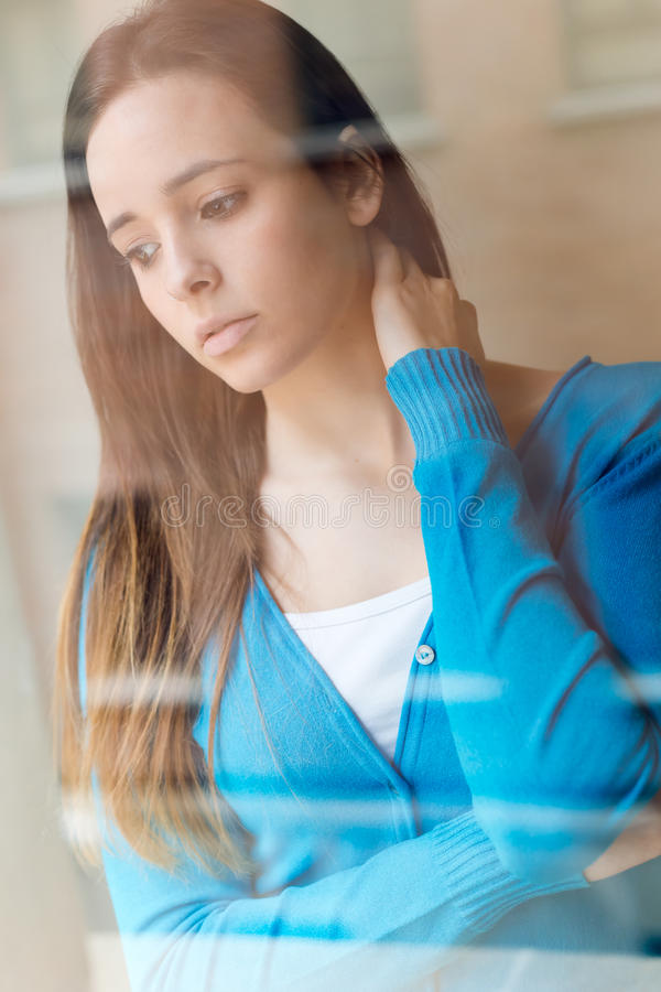 Depressed young woman sitting at home. stock photo