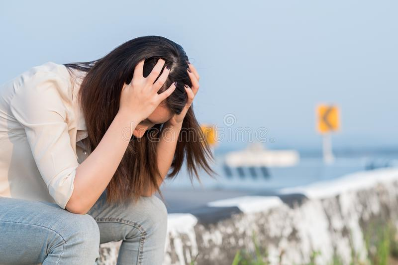 Depressed young woman sitting near a road royalty free stock photo