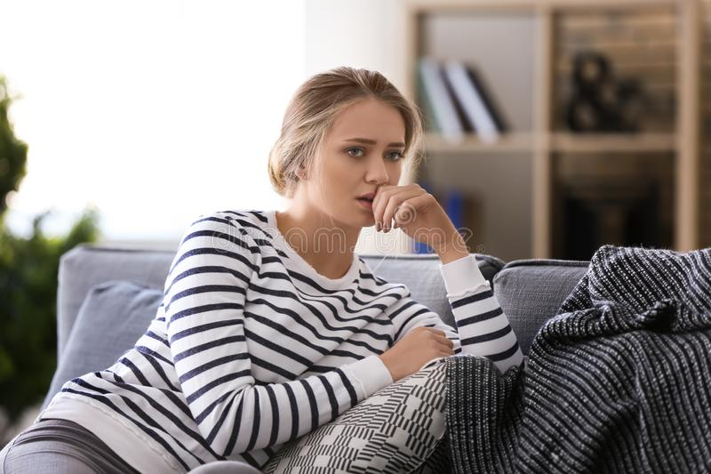 Depressed young woman sitting on sofa at home stock images