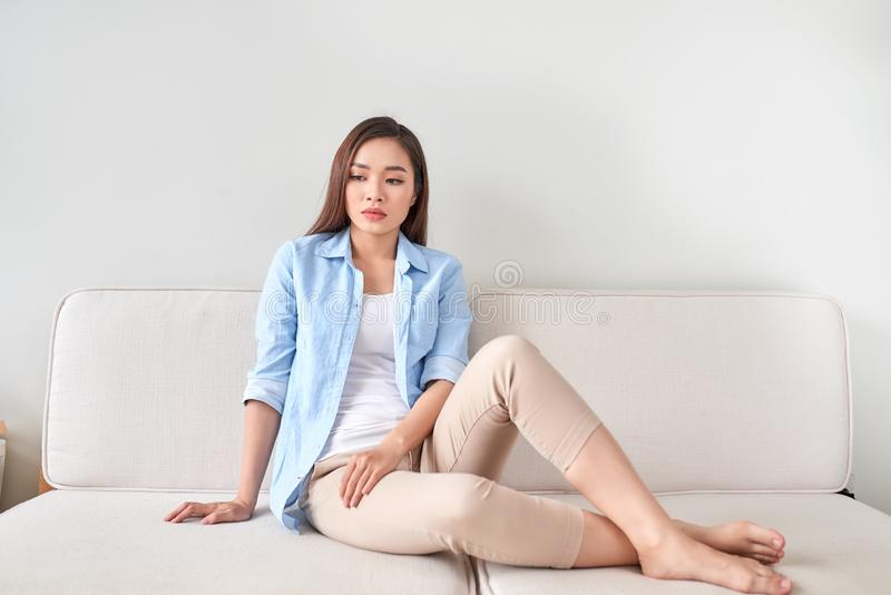 Depressed young woman sitting on sofa at home stock photos
