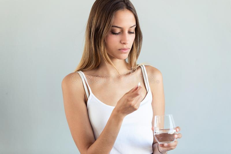 Depressed young woman taking pills over gray background royalty free stock photo