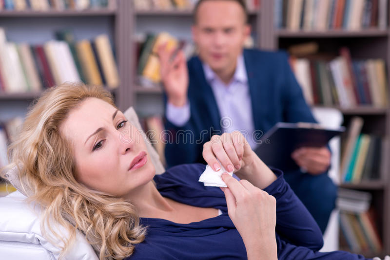 Depressed young woman talking to her therapist stock image