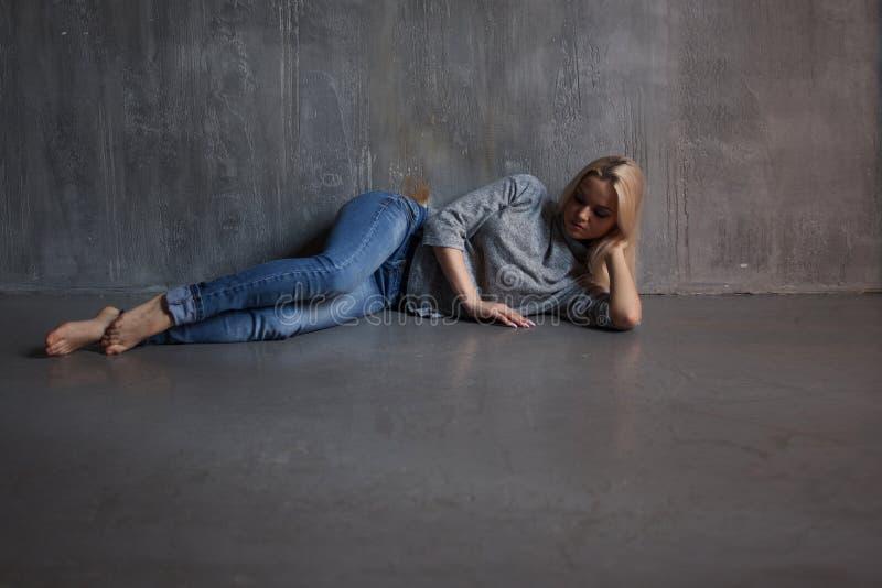 depressie Jonge vrouw die op de vloer ligt stock afbeelding