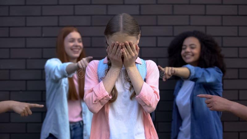 Depressief pesterend slachtoffer dat zijn gezicht bedekt met handen, klasgenoten die met de vingers wijzen royalty-vrije stock foto