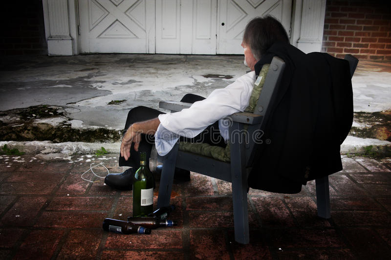 Depression. A sad depressed man in a chair with a old building facing him. Concept for depression or inablity to cope stock photo