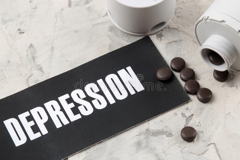 Depression concept. Psychological illness. the word depression on paper and pills on a light background. top view royalty free stock photography