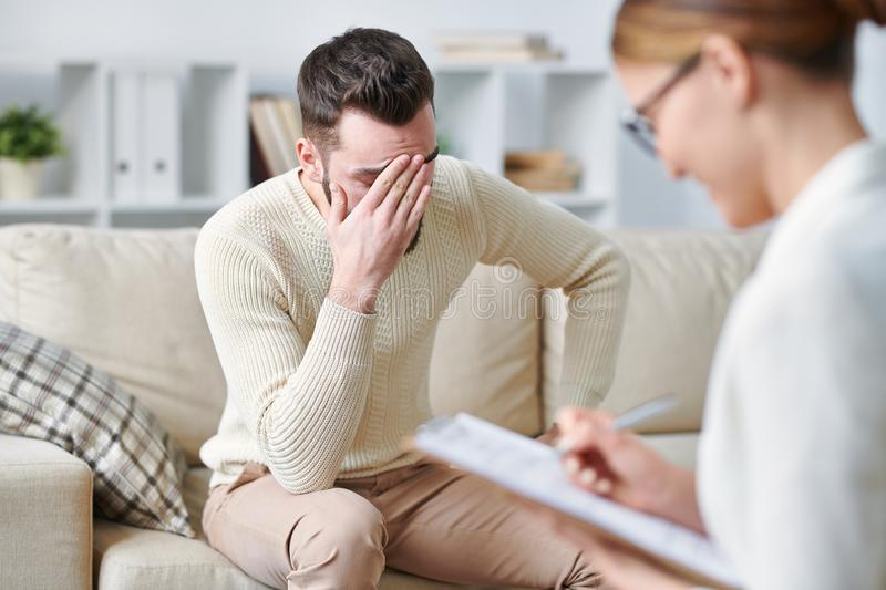 Depression. Depressed young patient with face palm expression sitting on couch in front of counselor making notes during their interaction stock photography