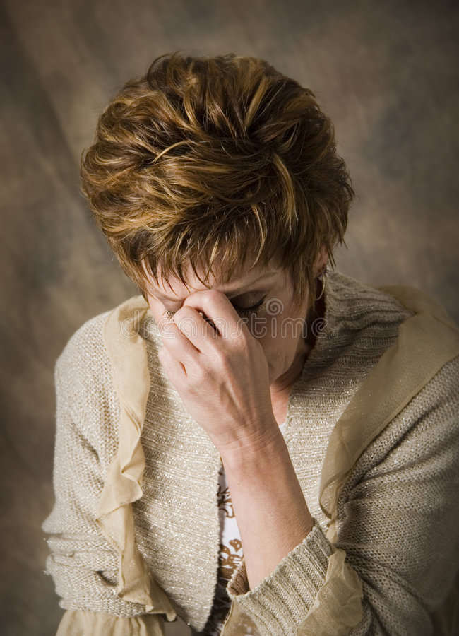 Depression and Sorrow. Troubled mature woman with hand on face royalty free stock image