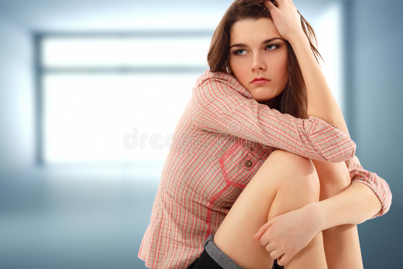 Depression teen girl lonely in empty room stock photography