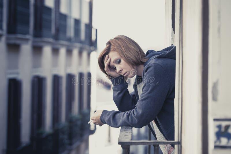 Depressione e sforzo di sofferenza della giovane donna all'aperto al balcone fotografia stock