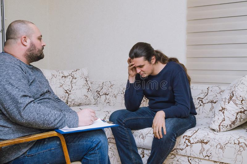 Depressive man in stress visits a psychologist. Psychologist listening and writing notes. Depressive men in stress visits a psychologist. Psychologist listening royalty free stock photos