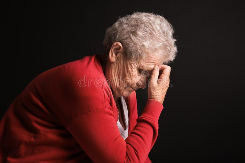 Deprimerad äldre kvinna på mörk bakgrund arkivbild