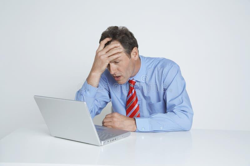 Deprimerad affärsman Looking At Laptop royaltyfria bilder