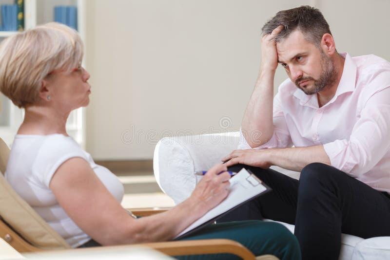 Deprimerad affärsman med psykoanalytikern royaltyfri bild