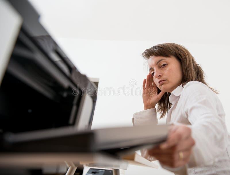 Deprimerad affärsperson som arbetar med skrivaren arkivbild