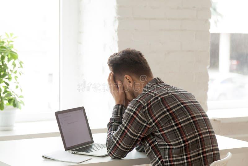 Deprimerad arbetare som känner sig ner att avfyras via email royaltyfri bild