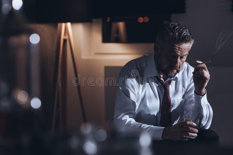 Deprimerad arbetsnarkoman som röker cigaretten royaltyfri fotografi