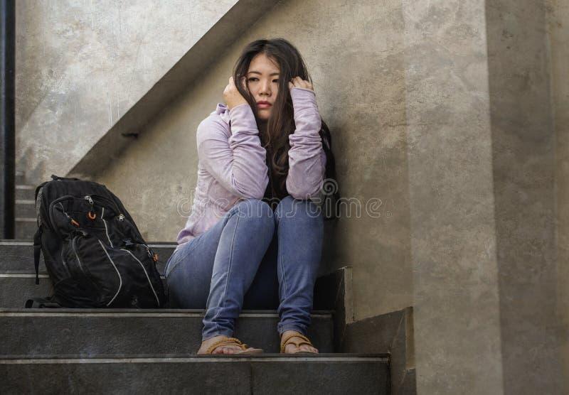 Deprimerad asiatisk amerikansk studentkvinna eller hunsad tonåring som utomhus sitter på förkrossad och angelägen känsla för gata arkivbild