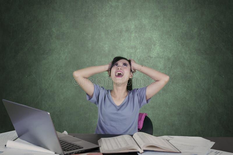 Deprimerad högskolestudent som skriker i klassrumet arkivfoton